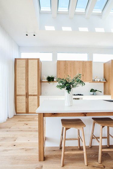 greenery in vase on white and wood kitchen island