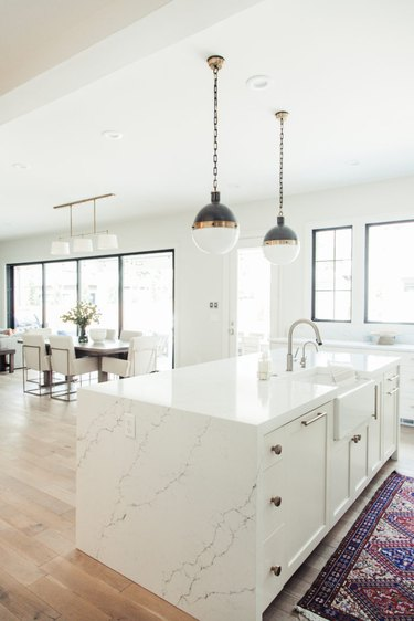 open concept white kitchen with vintage rug and modern pendant lights