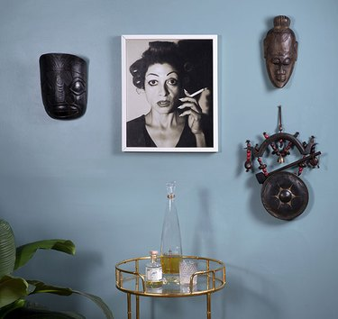 Baby blue wall with photograph and masks in Monica Orozco's living room