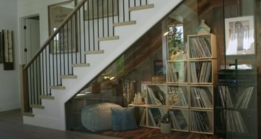 stairs with space with glass doors and record player and records inside