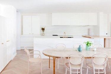 white kitchen with chevron wood flooring