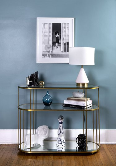 Baby blue wall with photograph and table in Monica Orozco's living room