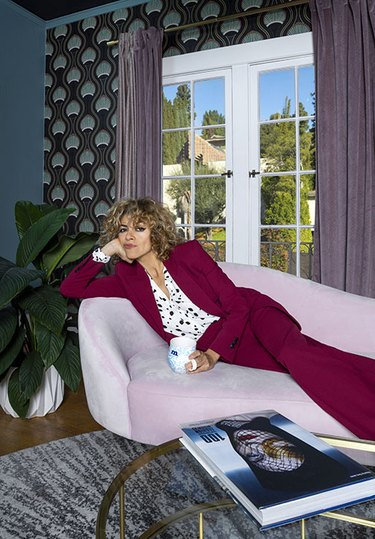 Photographer Monica Orozco wearing a suit in her colorful Hollywood Regency–inspired living room