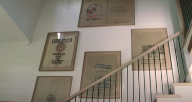 framed coffee bags on wall near staircase