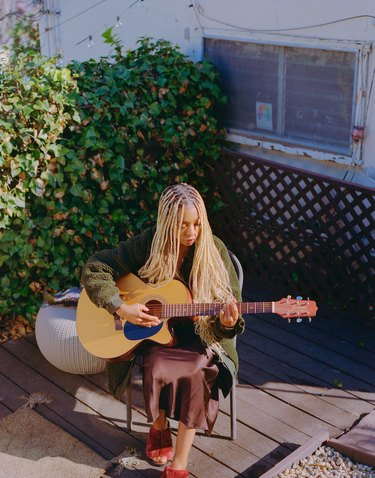 person sitting outside with guitar