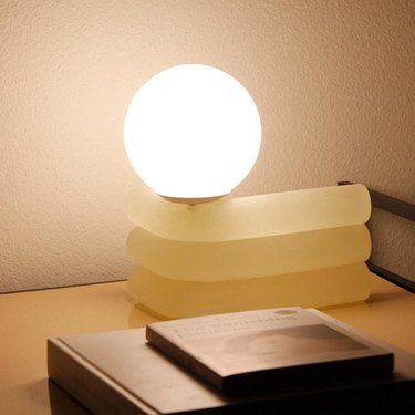 elio lamp with globe light near books