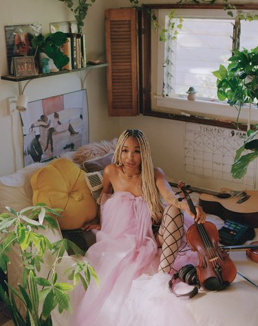 person in pink tulle dress sitting near window, shelf, and plants