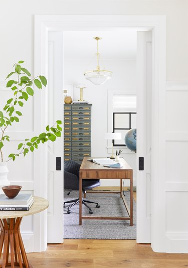 white home office with vintage decor and glass pendant light
