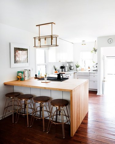 Small kitchen with wood waterfall island, bar stools, white cabinets, wood floor, pendant light.