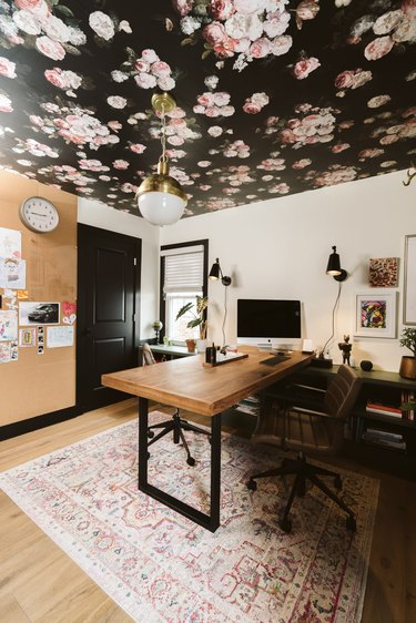 modern home office with wood desk and pendant light hanging from floral ceiling