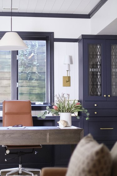 traditional home office with blue built-ins and white fabric pendant light