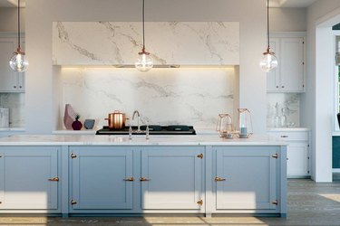 blue kitchen with engineered stone countertop and backsplash