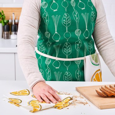 person with green apron near counter with cutting board and towel