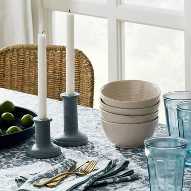 table with bowls and white candles in soapstone candlesticks