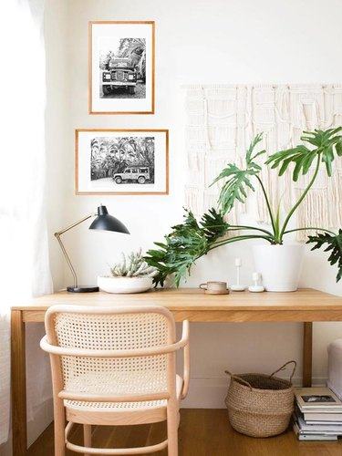 a neutral office with black and white photos and macramé on the wall