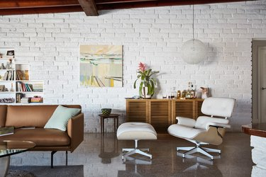 living room space with couch and eames chair and hanging light fixture