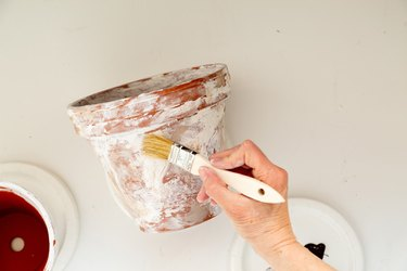 applying plaster to DIY aged terra cotta pots
