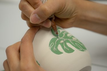 person painting leaf on ceramic piece