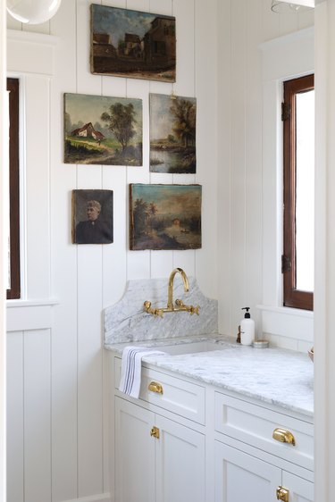 white farmhouse butler's pantry with sink and vintage oil paintings