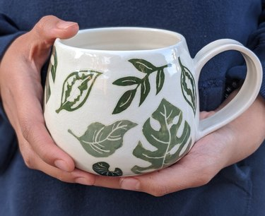 mug with plant pattern being held in a person's hands