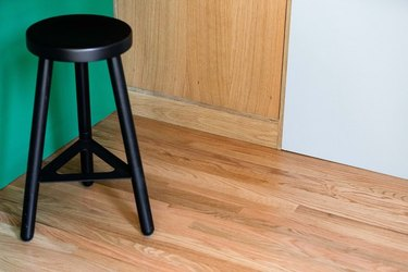 Bamboo floors, black bar stool, green wall.
