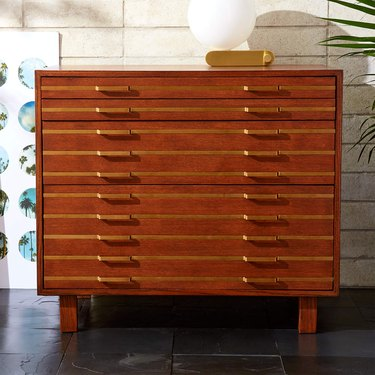 oak file cabinet with inlaid brass in modern space