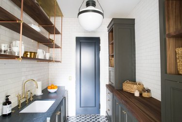 butler's pantry with subway tile walls and open shelving
