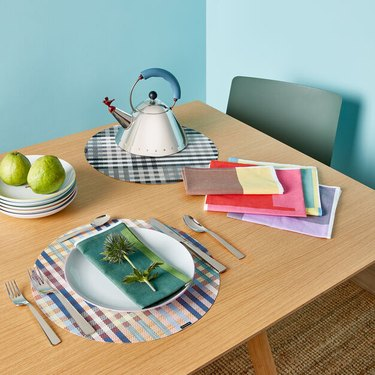wood table with kettle, dishes, and cloth napkins on checkered placemats