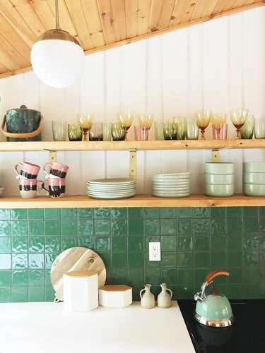 white and wooden kitchen with green square tile backsplash