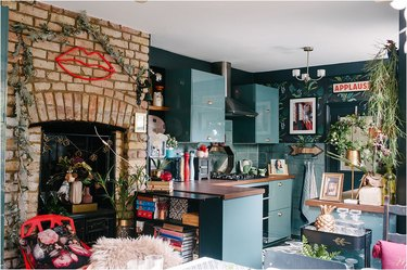 green kitchen with green backsplash and tropical wallpeper