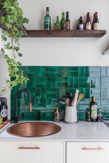 white kitchen with bronze sink and green glazed tile backsplash