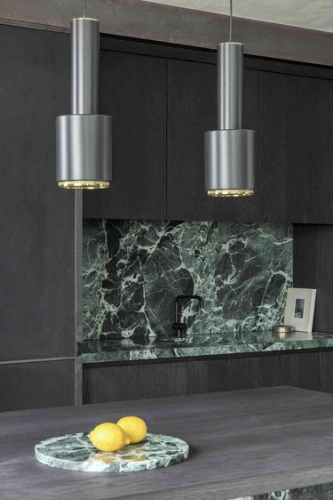 dark wood kitchen with green marble countertop and bacskplash
