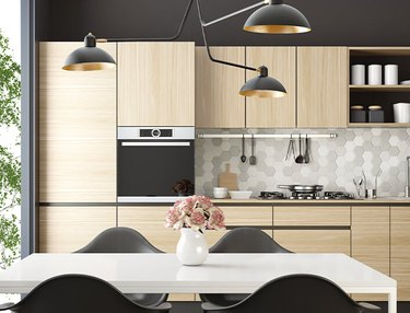 Kitchen with bamboo cabinets, stove, modern lamp, table and chairs.