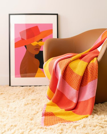 framed art next to chair with colorful blanket