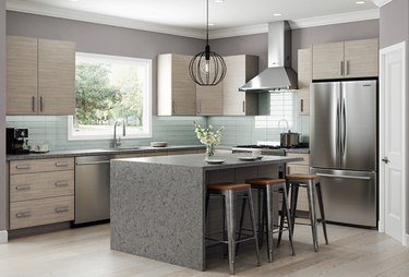 Kitchen with bamboo cabinets, waterfall island, barstools, pendant lamp, stainless appliances.