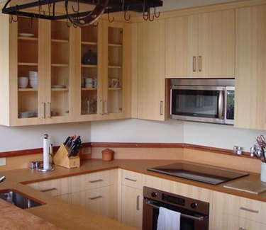 Kitchen with bamboo cabinets, microwave, electric cooktop.