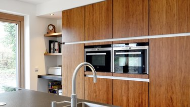 kitchen with bamboo cabinets, ovens in wall, open shelves.