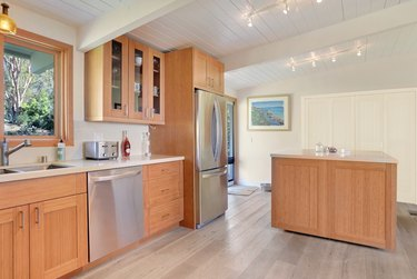 Kitchen with bamboo cabinets, track lighting, wood floors, stainless appliances.