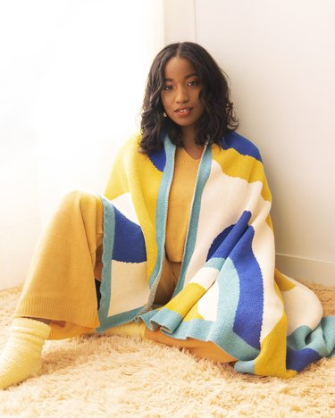 person wearing yellow outfit with colorful blanket