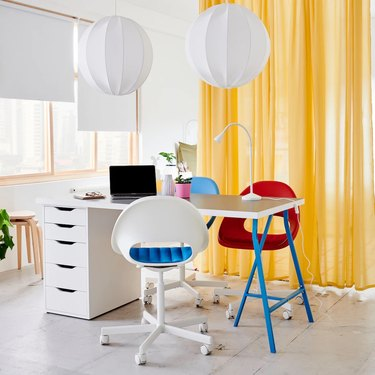 white and yellow home office with yellow curtain divider, red desk chair