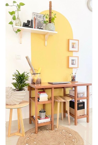 white home office with yellow accent wall, floating shelf on the wall with plants