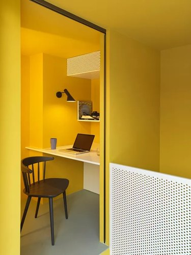 minimalist yellow home office with built-in desk and black desk chair