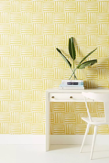 yellow home office with white and yellow wallpaper behind a white desk