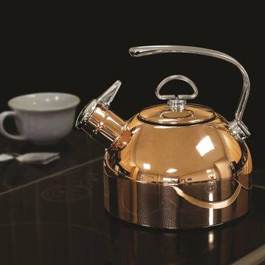 rose gold tea kettle on black stove