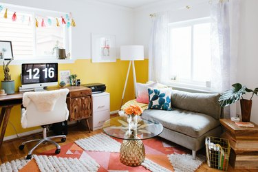 white home office with yellow colorblock, orange and pink rug