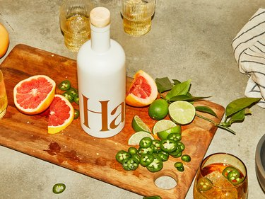 white bottle on wood cutting board with fruit