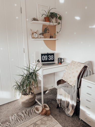 small home office with white floating shelves and painted half circle
