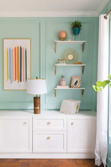 white open shelves with brass brackets in sea green office