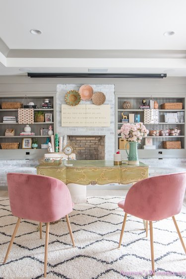 pastel basement office with built-in shelves and pink chairs