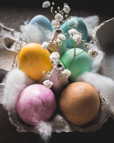 naturally dyed easter eggs in carton with baby's breath